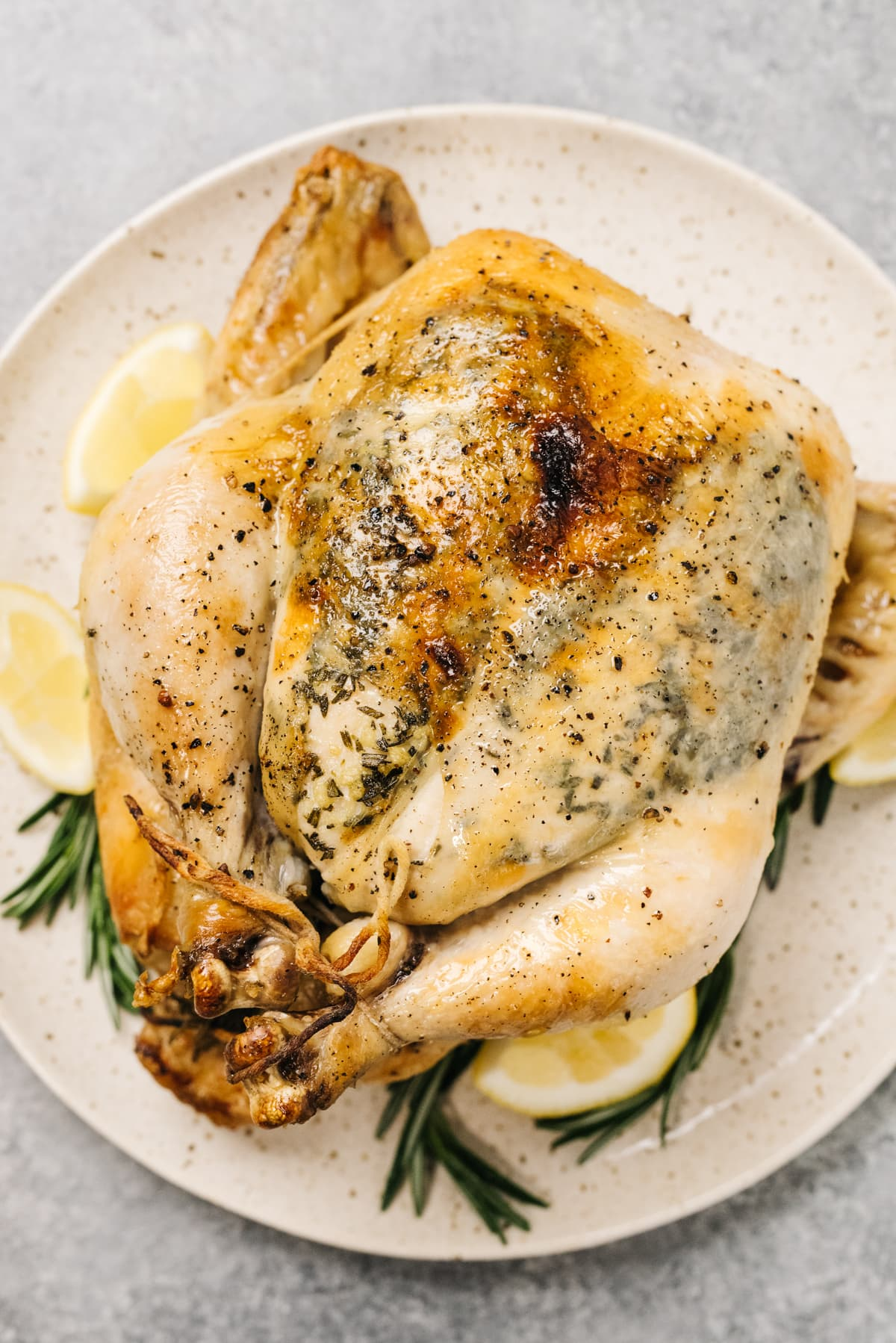 A slow cooker whole chicken on a platter with fresh herbs and lemon wedges for garnish.