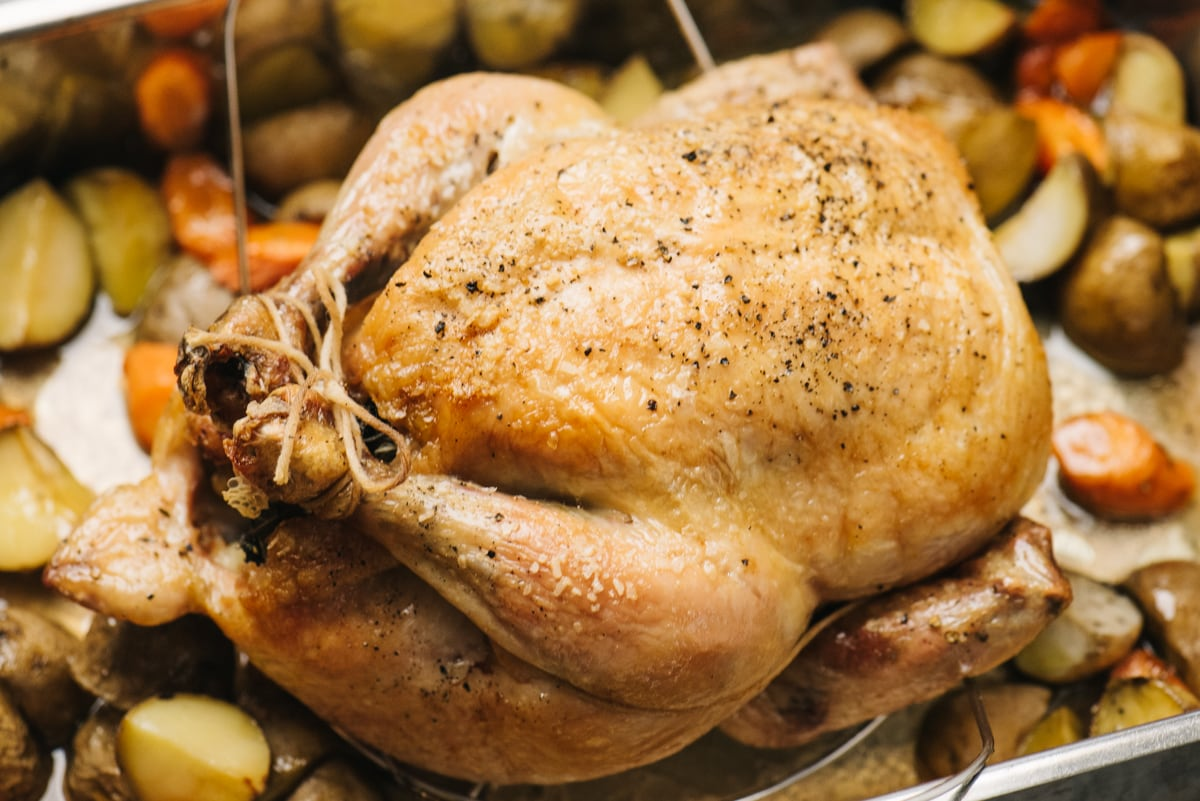 A whole roasted chicken in a roasting pan surrounded by oven roasted potatoes and carrots.