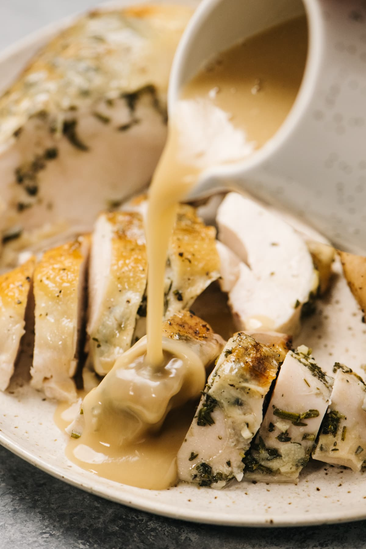 Pouring gravy over sliced roasted chicken on a tan speckled plate.
