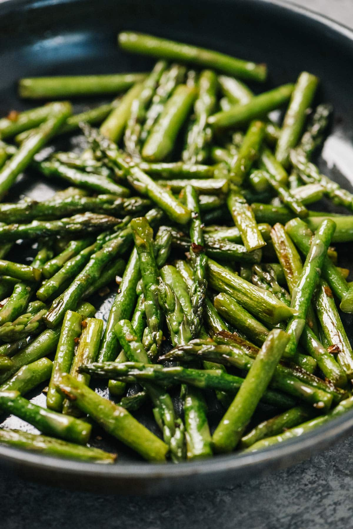 Side view, sautéed asparagus in a skillet.