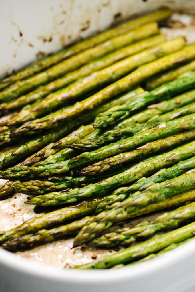 Side view, baked asparagus with balsamic vinegar in a casserole dish.