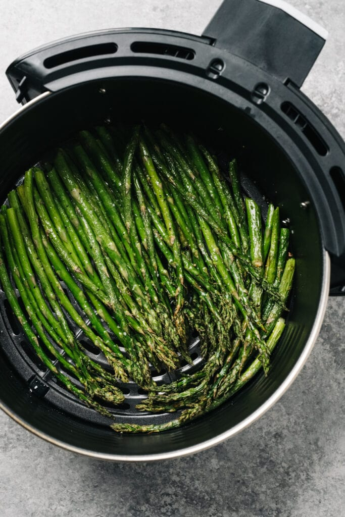 Cooked asparagus spears in the basket of an air fryer.