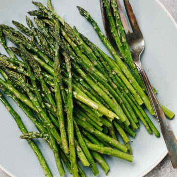 Cooked asparagus on a blue platter with a silver serving fork.