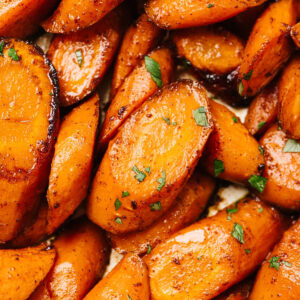 Sliced baked carrots garnished with chopped parsley.