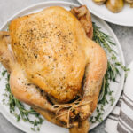 A whole roasted chicken on a white platter surrounded with fresh herbs for garnish.