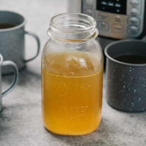 A mason jar of bone broth and 3 mugs of bone broth in front of an instant pot.
