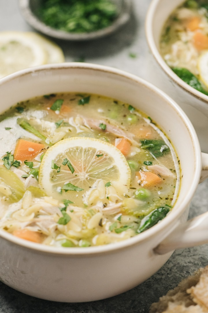 Side view, a bowl of lemon chicken orzo soup garnished with fresh parsley and a lemon wheel.