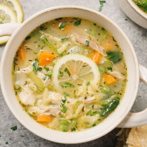 A bowl of lemon chicken orzo soup garnished with a lemon wheel and fresh parsley on a concrete background surrounded by a bowl of chopped parsley, lemon slices, and crusty bread.