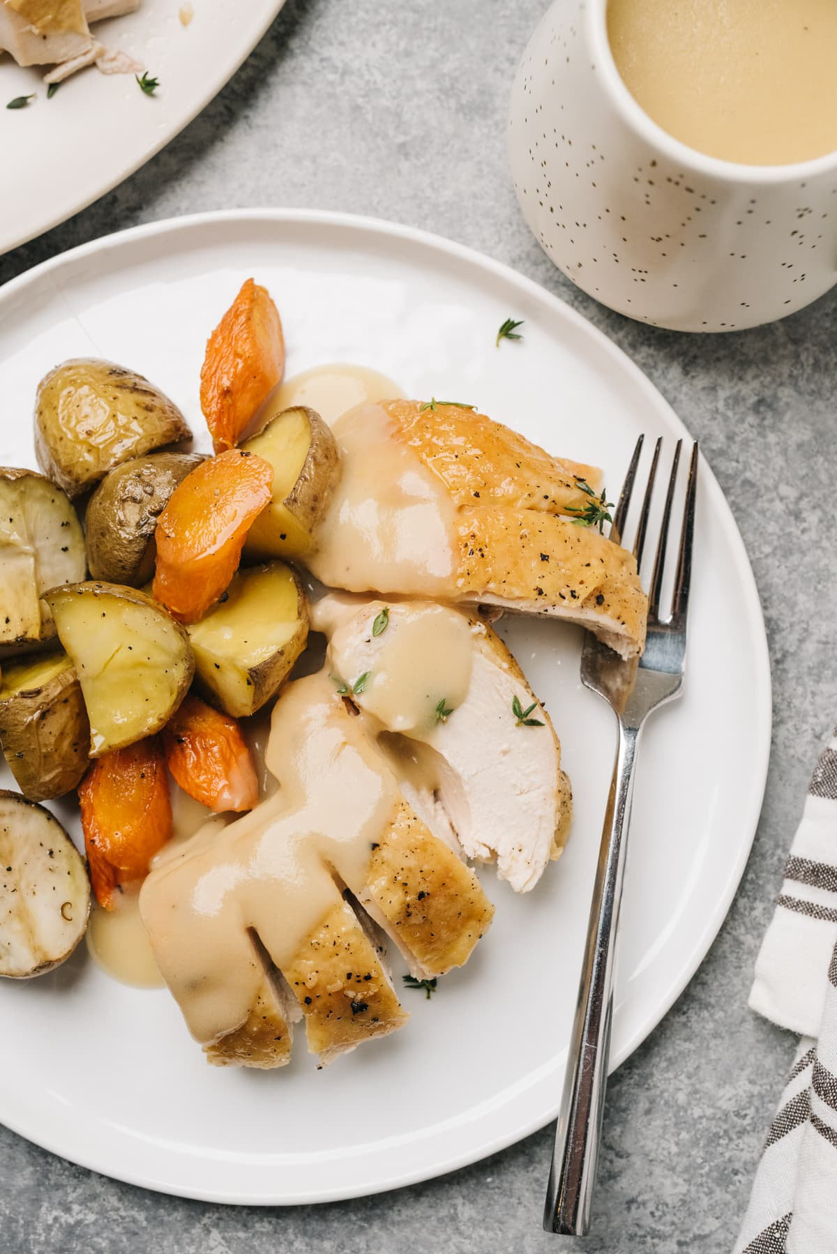 Sliced roasted chicken breast on a plate drizzled with gravy, with roasted potatoes and carrots and a small pitcher of gravy to the side.