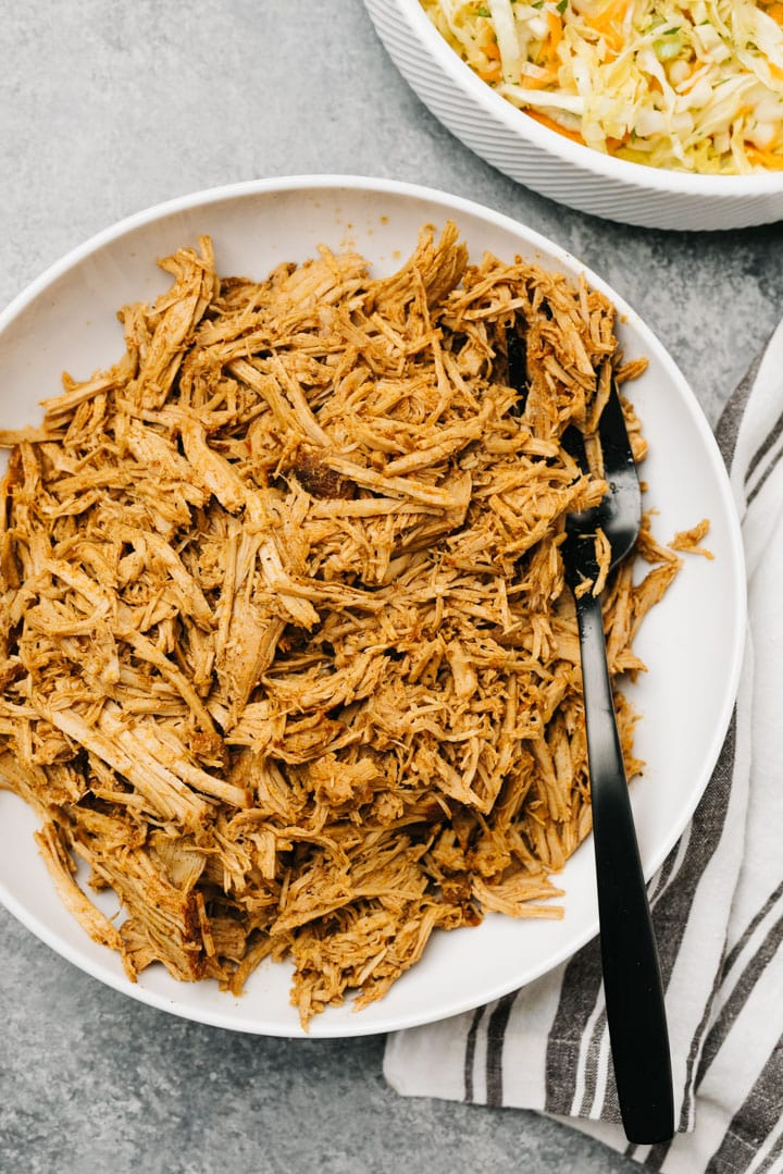 A bowl of slow cooker pulled pork with a black serving spoon and striped linen napkin.