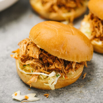 Three pulled pork sandwiches with coleslaw on buns.