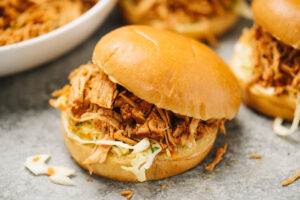 Two pulled pork sandwiches with coleslaw on a grey background, with a bowl of slow cooker pulled pork in the background.