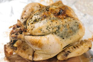 A whole slow cooker chicken on a foil lined baking sheet after crisping skin under the broiler in the oven.