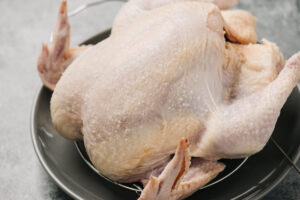 Side view, a dry brined whole chicken on a grey plate.