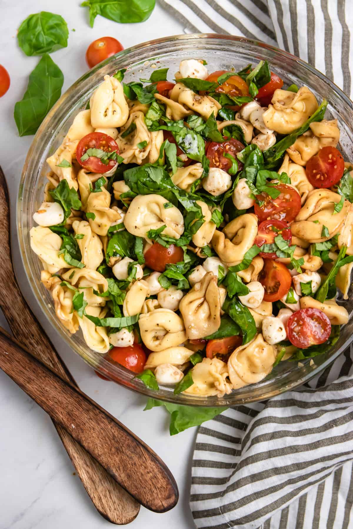 A caprese and tortellini pasta dinner salad in a large glass serving bowl with wood serving spoons on the side.