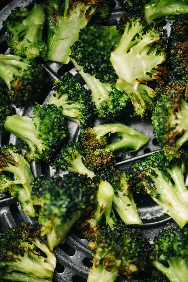 Cooked broccoli florets in an air fryer basket.