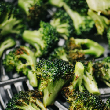 Side view, cooked broccoli florets in the basket of an air fryer.
