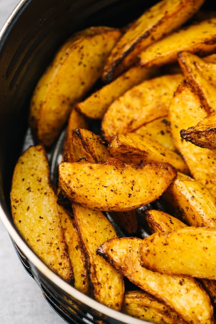 Side view, crispy potato wedges in the basket of an air fryer.