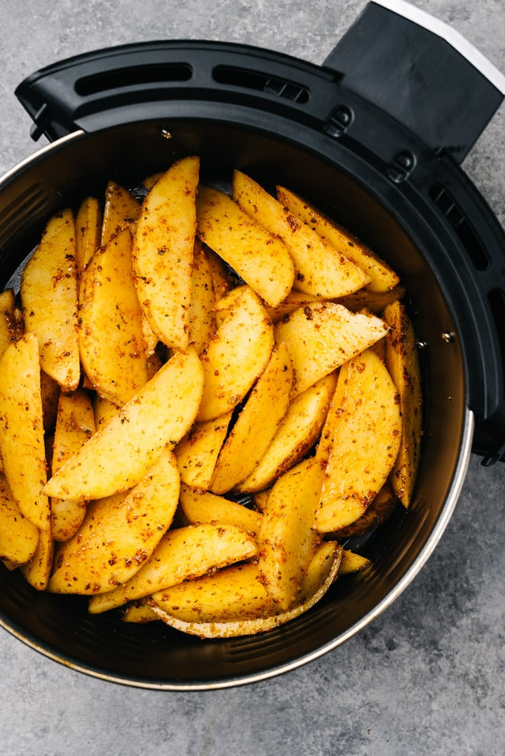 Potato wedges tossed with olive oil and seasoning in the basket of an air fryer.