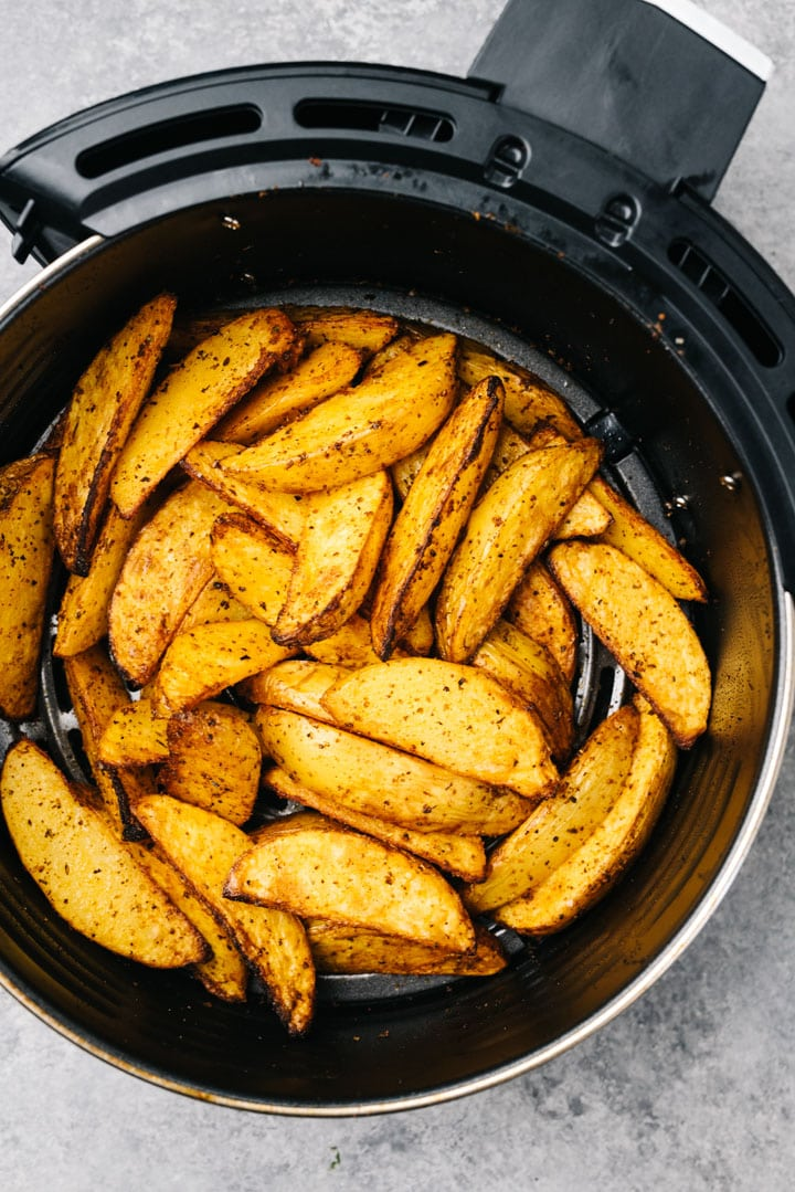 Crispy cooked potato wedges in the basket of an air fryer.
