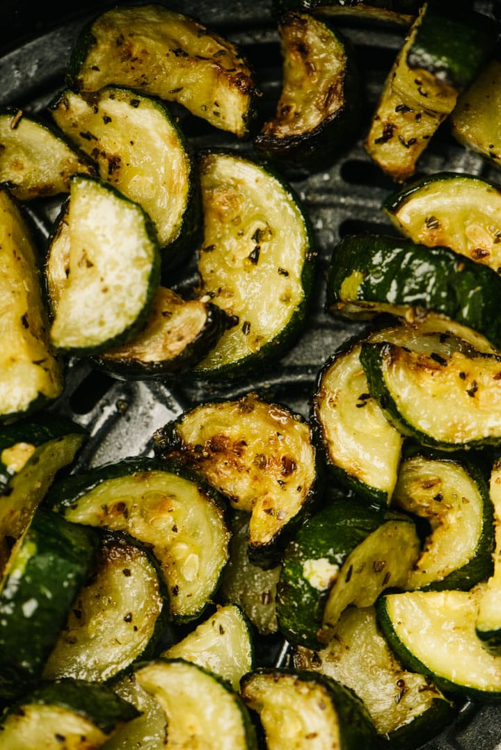 From overhead, a detail of sautéed zucchini in the basket of an air fryer.