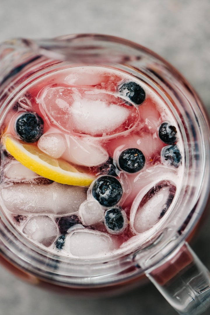 From overhead, a close up shot of a pitcher of blueberry lemonade.