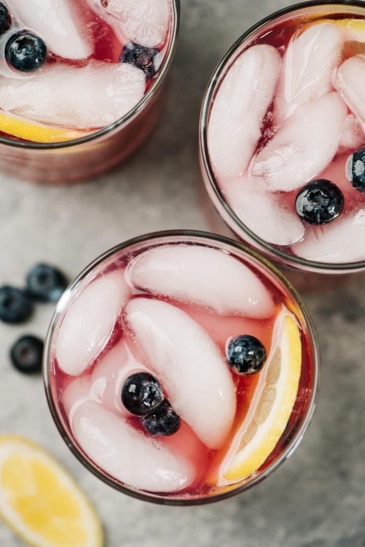 From overhead, three glasses of homemade blueberry lemonade.
