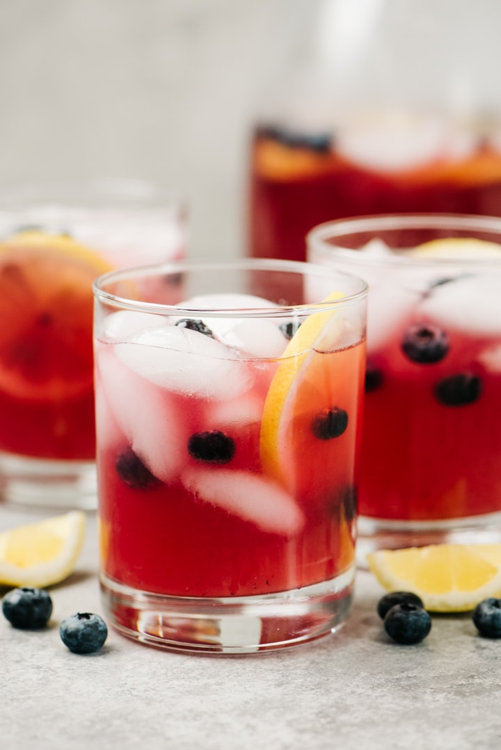 Three glasses and a pitcher of blueberry lemonade on a concrete background with lemon wedges and fresh blueberries scattered around the glasses.