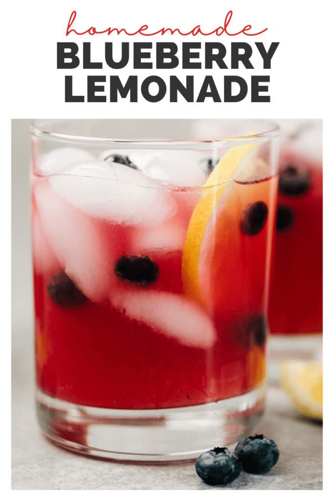 """Two glasses of blueberry lemonade on a concrete background with a title bar that reads """"homemade blueberry lemonade""""."""