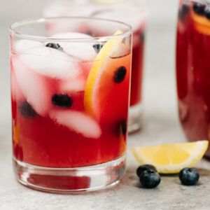 Two glasses and a pitcher of blueberry lemonade on a concrete background with lemon wedges and fresh blueberries scattered around the glasses.