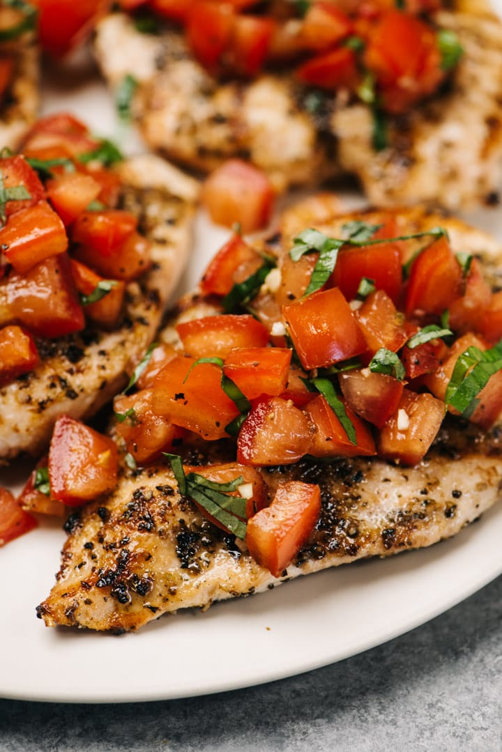 Side view, grilled chicken breasts topped with tomato bruschetta on a cream serving platter.