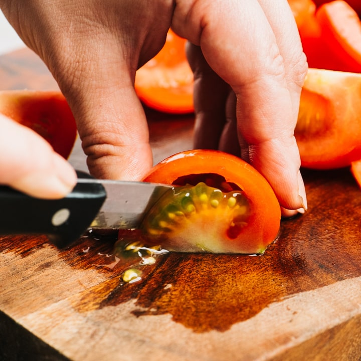 Removing the seeds from a quartered tomato on a cutting board.