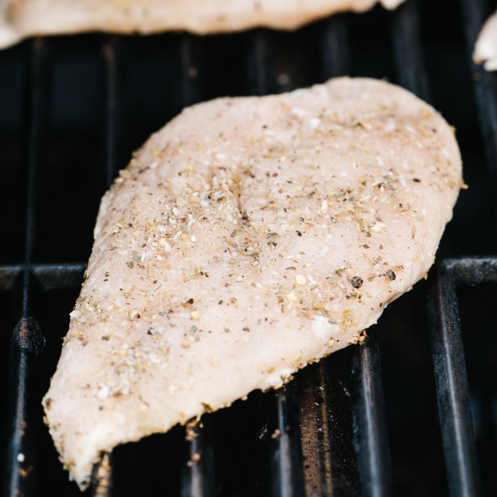 A seasoned chicken breast on a grill.