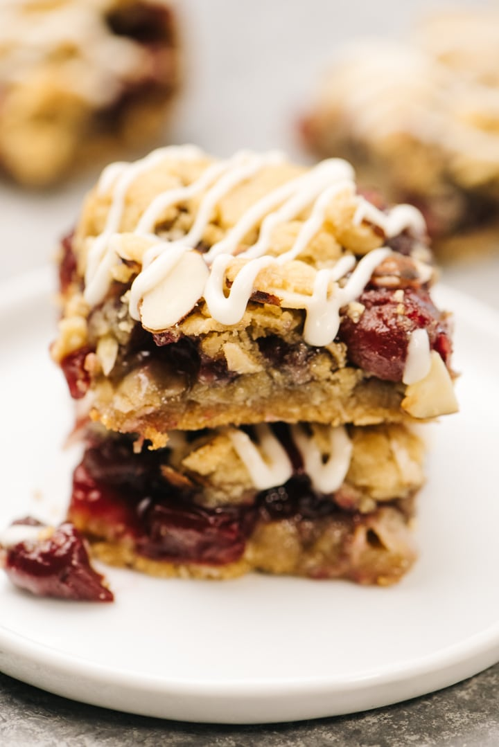 Two cherry pie bars stacked on a white plate with additional bars in the background.