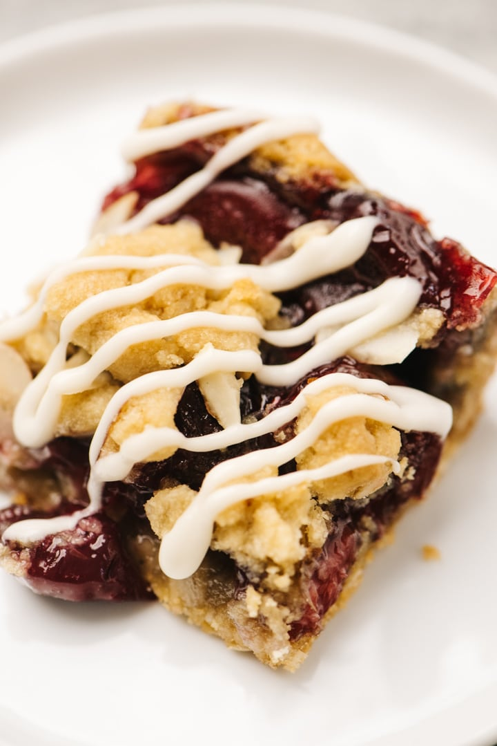 Side view, a single cherry pie bar on drizzled with vanilla glaze on a white plate.