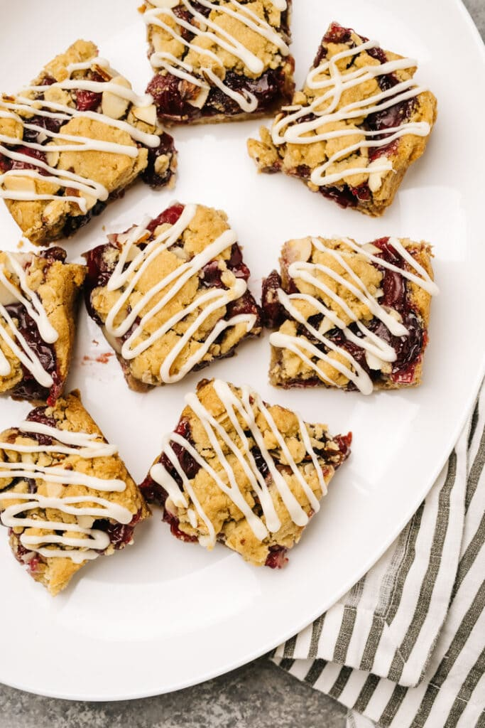 Cherry pie bars on a white platter, drizzled with vanilla icing.