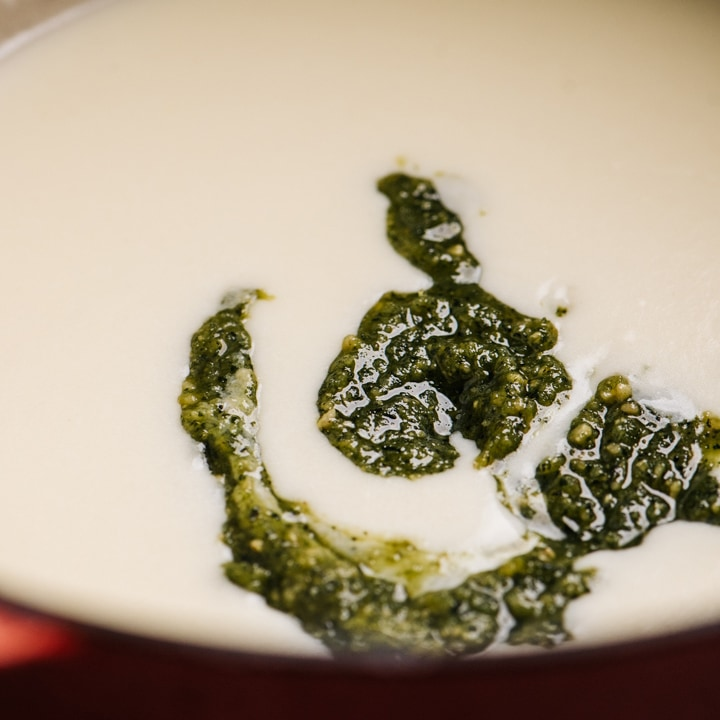 Pesto sauce added to creamy pasta sauce in a dutch oven.