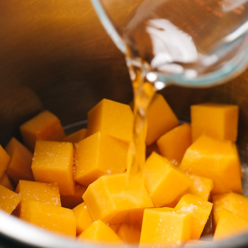 Pouring water into an instant pot with diced butternut squash.