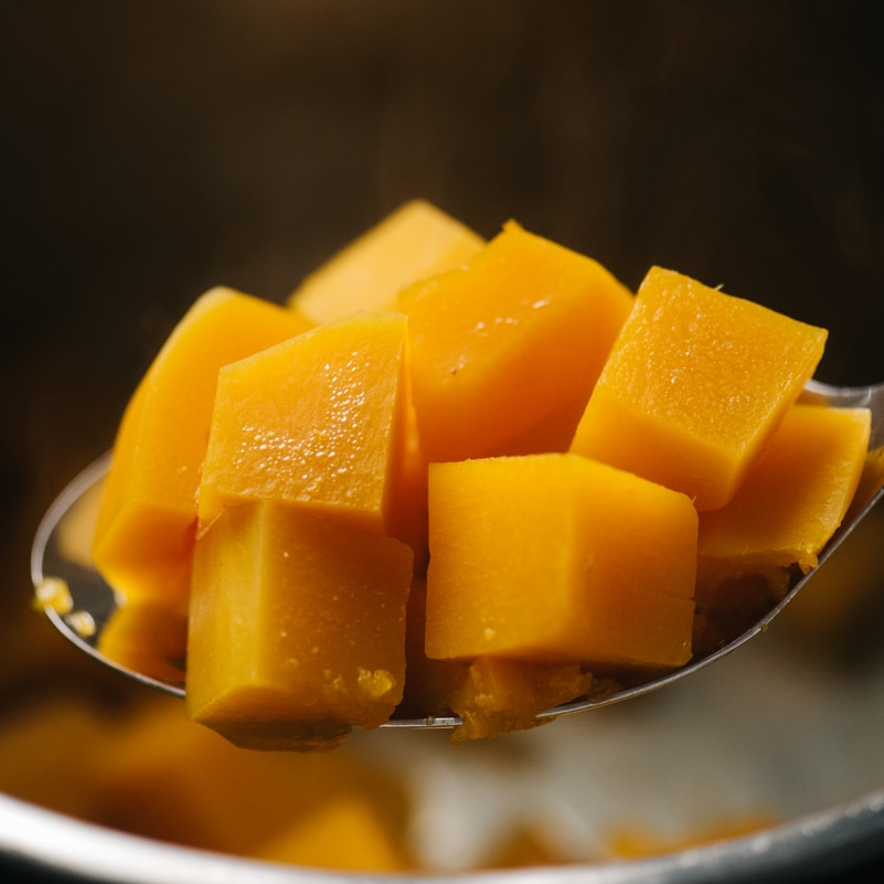 Steamed butternut squash cubes on a slotted spoon hovering over the inner pot.