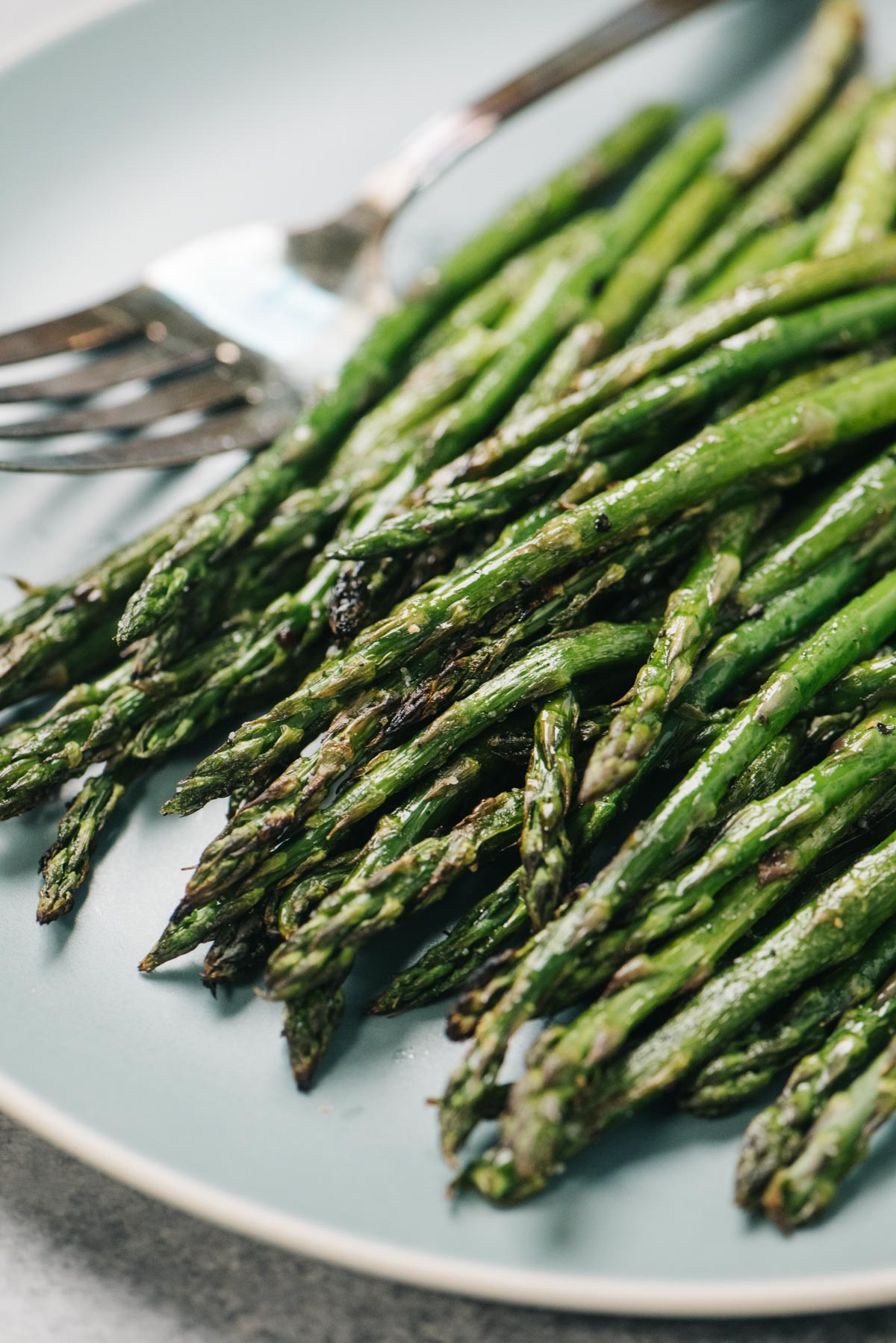 Side view, grilled asparagus spears on a blue serving plate with a silver serving fork.