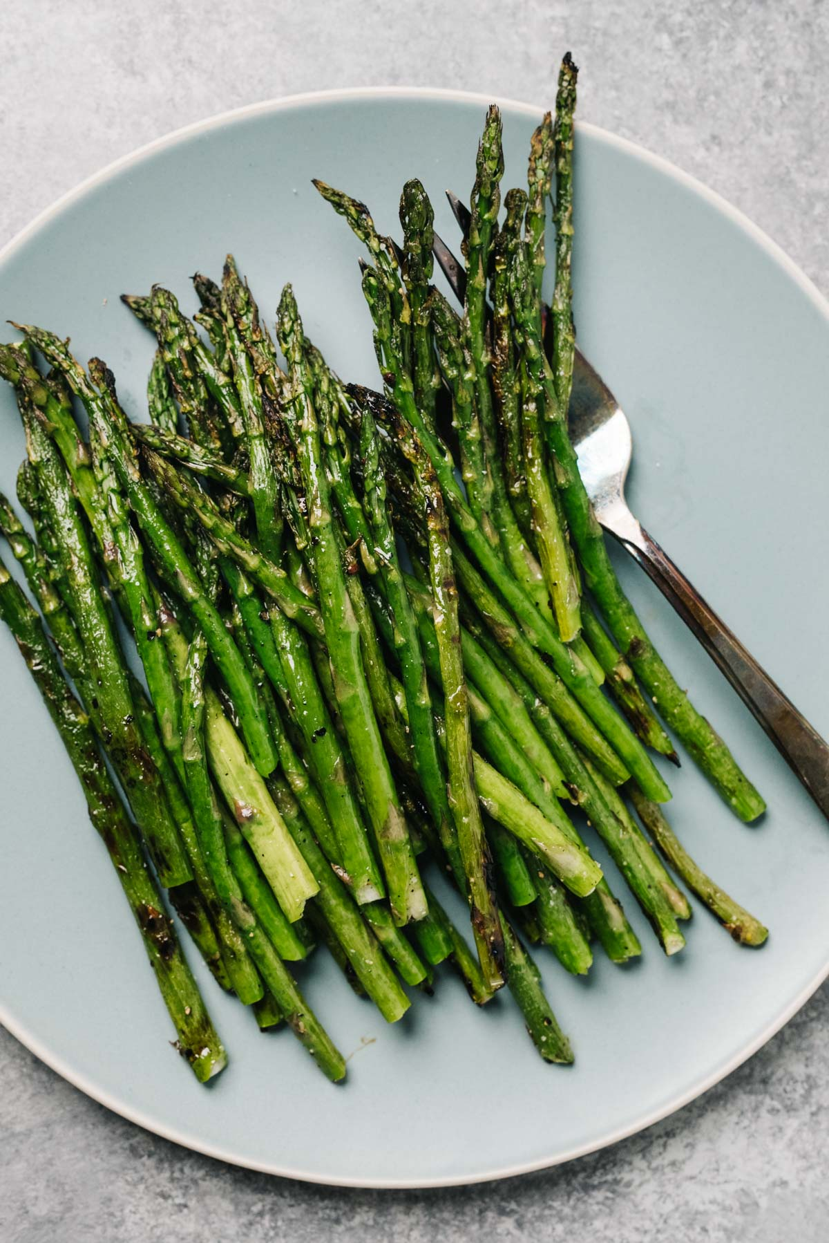 Grilled asparagus spears on a blue plate with a silver serving spoon.