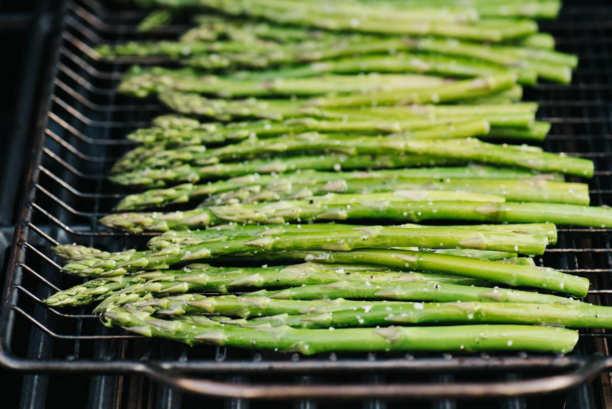 Side view, asparagus spears in a grilling tray over a grill.