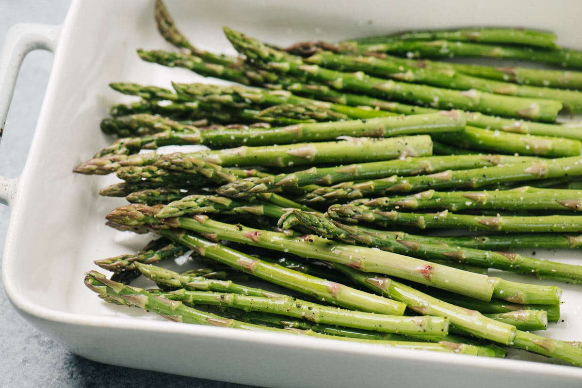 Side view, asparagus spears tossed with olive oil, balsamic vinegar, and seasonings in a casserole dish.