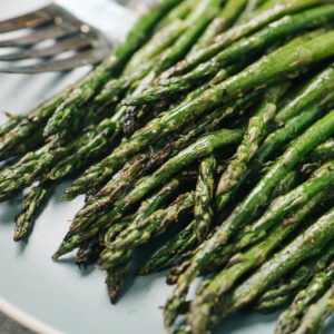 Side view, grilled asparagus on a blue plate with a serving fork in the background.