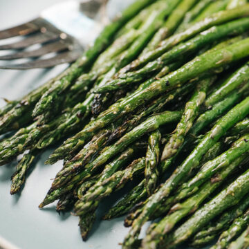 Side view, grilled asparagus on a blue plate.
