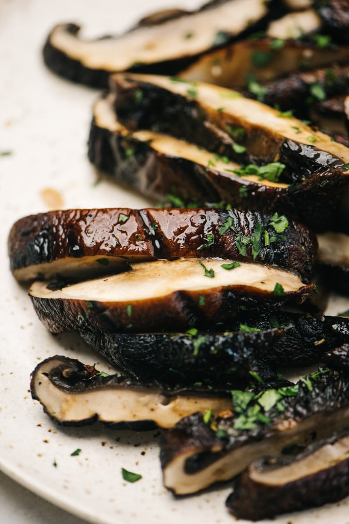 Sliced grilled portobello mushrooms on a tan speckled plate, garnished with fresh herbs.