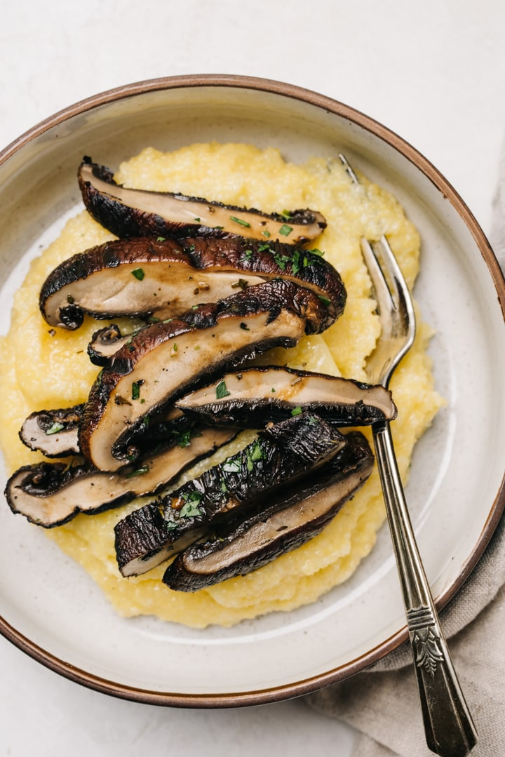 Slices of grilled portobello mushrooms over polenta in a tan and black bowl with silver fork.