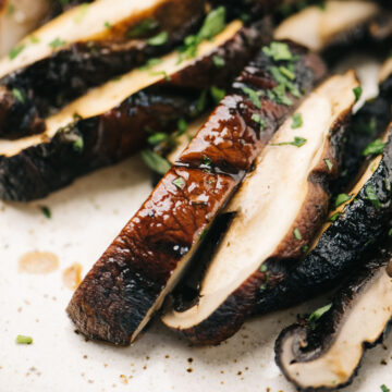 Side view, sliced grilled portobello mushrooms on a tan speckled plate, garnished with fresh herbs.