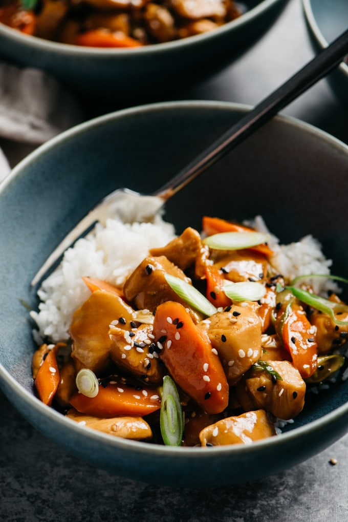 Side view, honey garlic chicken stir fry in a blue bowl served over white rice with silver fork on a cement background.