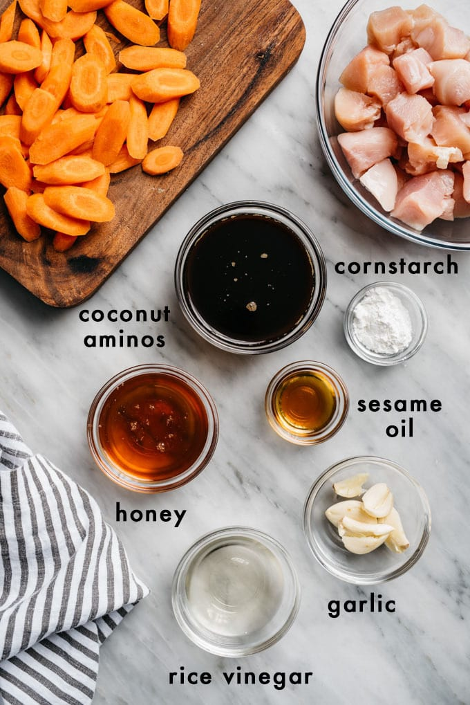 The ingredients for honey garlic chicken in prep bowls arranged on a marble background.